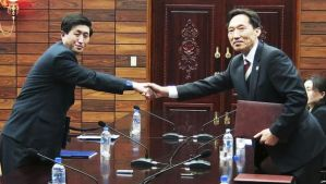 Head of the South Korean working-level delegation Lee Duk-haeng, right, shakes hands with his North Korean counterpart Park Yong Il after an agreement to allow families separated since the war between the two countries to reunite was signed at Tongilgak in the North Korean side of Panmunjom on Wednesday, February 5, 2014. (AP Photo/South Korean Unification Ministry)