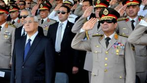 In this July 22, 2013 file photo released by the Egyptian Presidency, Egypt's interim President Adly Mansour, front left, Defense Minister Field Marshal Abdel-Fattah El-Sisi, front right, and other military officers listen to the national anthem during a medal ceremony at a military base in eastern Cairo. (AP Photo/Sheriff Abd El Minoem, Egyptian Presidency/File)