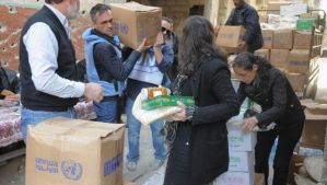 A handout picture released by the official Syrian Arab News Agency (SANA) on February 1, 2014 shows residents of Syria's besieged Yarmuk Palestinian refugee camp, south of Damascus, receiving food parcels from the United Nations Relief and Works Agency (UNRWA). (AFP Photo/HO/SANA)