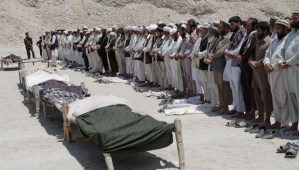 In this file photo taken Monday, June 3, 2013, Afghan men offer funeral prayers in front of the bodies of seven civilians killed by a roadside bomb in the Alingar district of Laghman province, east of Kabul, Afghanistan. The number of children killed and wounded in Afghanistan's war jumped by 34 percent in 2013 as the Taliban intensified armed attacks across the country and continued to lay thousands of roadside bombs, according to a U.N. report Saturday, Feb. 8, 2014. (AP Photo/Rahmat Gul, File)