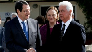 Cyprus president Nicos Anastasiades, left, and Turkish Cypriot leader Dervis Eroglu shake hands as U.N. Secretary-General's Special Representative to Cyprus Lisa Buttenheim, center, smiles after their meeting at a UN compound in the UN buffer zone in the divided capital Nicosia, Cyprus, Tuesday, Feb. 11, 2014. The leaders of Cyprus' Greek and Turkish Cypriot communities are embarking on a new round of talks aimed at achieving the long-elusive goal of reunifying the ethnically split island nation. (AP Photo/Petros Karadjias)