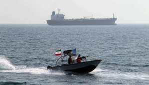 A picture taken on July 2, 2012 shows Iranian Revolutionary Guards driving a speedboat in front of an oil tanker at the port of Bandar Abbas. (AFP PHOTO/ATTA KENARE)
