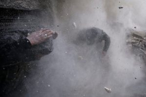 Goran Tomasevic, a Serbian photographer working for Reuters, won the 1st Prize Spot News Stories category of the 2014 World Press Photo contest with his series of pictures which includes this one of Syrian rebel fighters taking cover amid flying debris and shrapnel after being hit by a tank shell in the Ain Tarma neighborhood of Damascus, taken on January 13, 2013. (REUTERS/Goran Tomasevic)