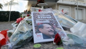 Flowers are laid at a memorial for slain opposition leader Chokri Belaid (portrait) set up at the site where he was murdered one year ago, on February 6, 2014 in Tunis. Tunisians today marked 12 turbulent months since the assassination of opposition politician Chokri Belaid, with his family still demanding to know what happened despite the alleged assassin being shot dead this week. AFP PHOTO / FETHI BELAID