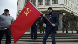A local resident holds a Soviet flag as members of Cossack militia guard the local parliament building in Simferopol, in Ukraine's Crimea region, on Thursday, March 6, 2014. (AP Photo/Ivan Sekretarev)