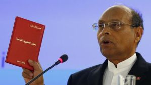 Tunisia President Moncef Marzouki holds a copy of the Tunisian new constitution during his address to the 25th session of the Human Rights Council at the United Nations in Geneva, Switzerland, on March 3, 2014. (Reuters/Denis Balibouse)