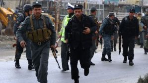 Afghan policemen run as they arrive near the Afghan election commission during an attack on the election centre in Kabul on March 29, 2014. (AFP PHOTO/WAKIL KOHSAR)