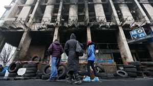 epa04109563 Ukrainians look on a burned during protests building near of the Independence Square in Kiev, Ukraine, 04 March 2014. Russian President Vladimir Putin met with journalists at his Novo-Ogaryovo residence outside Moscow to explain his position on the Ukrainian events, saying that he sees no need to send Russian troops to Ukraine now, calling it a 'last resort.' The Russian army reportedly had occupied key sites in the autonomous region of Crimea, where a majority of the population is ethnic Russian two days earlier. Troops surrounded several small military outposts and demanded Ukrainian troops disarm. EPA/SERGEY DOLZHENK