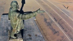 In this aerial photo a woman walks past a statue of Soviet Union founder Vladimir Lenin at the Russian leased Baikonur cosmodrome, in Kazakhstan, Thursday, March 27, 2014. Baikonur is the world's first and largest operational space launch facility. (AP Photo/Dmitry Lovetsky)