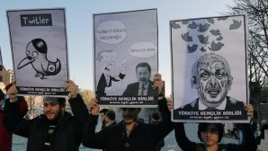 Members of the Turkish Youth Union hold cartoons depicting Turkey's Prime Minister Recep Tayyip Erdogan during a protest against a ban on Twitter in Ankara, Turkey, on Friday, March 21, 2014. (AP Photo/Burhan Ozbilici)