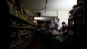 A supermarket seller stands near an emergency light during on of Cairo's many power outages at his shop on April 16, 2014. (REUTERS/Amr Abdallah Dalsh)