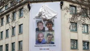 A poster calling for the release of French journalists Didier Francois, Edouard Elias, Nicolas Henin and Pierre Torres is installed on the facade of the Ile de france regional council headquarters in Paris January 6, 2014. (REUTERS/BENOIT TESSIER)
