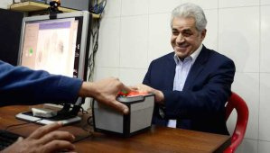 Hamdeen Sabahi has his hand print scanned as he registers his candidacy for president at an election office in Cairo, Egypt, on Thursday, April 3, 2014. (AP Photo/Ahmed Omar)