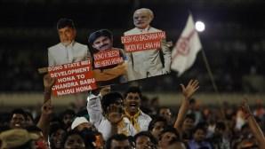 India's supports hold placard of Bharatiya Janata Party (BJP) prime ministerial candidate Narendra Modi, along with Telugu Desam Party president N. Chandrababu Naidu (L), Jana Sena party president Pavan Kalyan (C), during an National Democratic Alliance (NDA) election rally in Hyderabad, India, on April 22, 2014. (AP Photo/Mahesh Kumar A.)