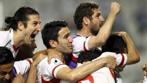 In this June 4, 2013, file photo, Iranian players celebrate after scoring the first goal during their 2014 World Cup Asian zone qualifying match between Qatar and Iran at the Al-Sadd stadium in Doha. (AP Photo/Osama Faisal, File)