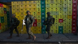 Army soldiers walk beside beer crates during an operation to occupy the Mare slum complex in Rio de Janeiro, Brazil, Saturday, April 5, 2014. More than 2,000 Brazilian Army soldiers moved into the Mare slum complex early Saturday in a bid to improve security and drive out the heavily armed drug gangs that have ruled the sprawling slum for decades. (AP Photo/Silvia Izquierdo)