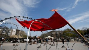 A flag flutters in the wind over barricades at the regional administration building that had been seized earlier, in Donetsk, Ukraine, on April 18, 2014. (AP Photo/Sergei Grits)