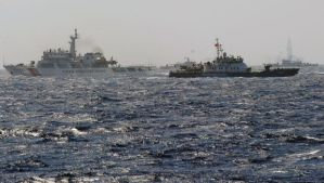 This picture taken from a Vietnam Coast Guard ship on May 14, 2014 shows a Vietnam Coast Guard ship (2nd R, dark blue) trying to make way amongst several China Coast Guard ships near to the site of a Chinese drilling oil rig (R, background) being installed at the disputed water in the South China Sea off Vietnam's central coast. Vietnam National Assembly's deputies gathered for their summer session are discussing the escalating tension with China over the South China Sea's contested water. AFP PHOTO/HOANG DINH Nam