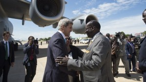 South Sudanese Foreign Minister Barnaba Marial Benjamin (C-R) greets US Secretary of State John Kerry (C-L) upon his arrival at Juba international airport on May 2, 2014. (AFP PHOTO / POOL / Saul LOEB)