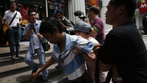 A plainclothes policeman detains a man (in the blue striped shirt) who had demonstrated against military rule by briefly holding up a protest sign at a shopping district in central Bangkok on May 31, 2014. (REUTERS/Erik De Castro)