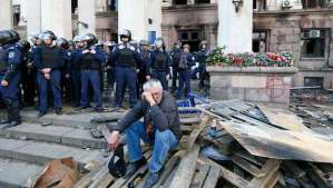 A man wearing a black and orange ribbon of St. George, a symbol widely associated with pro-Russian protests in Ukraine, reacts outside a trade union building where a deadly fire occurred, in Odessa, Ukraine, on May 3, 2014. Ukrainian Interior Ministry security forces members are seen in the background. (REUTERS/Gleb Garanich)