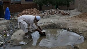 An elderly Afghan man collects water from a pool at a construction site in Kabul on May 31, 2014. (AFP PHOTO/Wakil Kohsar)