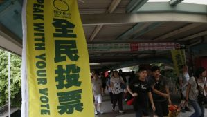A banner urging people to vote is displayed outside a polling station during an unofficial referendum in Hong Kong on June 22, 2014. (REUTERS/Bobby Yip)