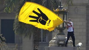 A student supporter of the Muslim Brotherhood and ousted Egyptian President Mohamed Mursi waves the yellow flag bearing the four-fingered Rabaa sign during a demonstration outside Cairo University on May 14, 2014. (REUTERS/Mohamed Abd El Ghany)