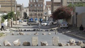 People walk on a street blocked by rocks after clashes between policemen and armed followers of the Houthi movement near the group's political bureau headquarters in Sana'a on June 21, 2014. (REUTERS/Khaled Abdullah)