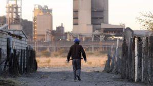 A township resident walks past Lonmin's Marikana platinum mine on June 13, 2014. (REUTERS/Skyler Reid)