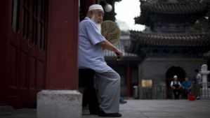 A Chinese Muslim man fans himself as he waits for the time to break his fast during the Muslim holy month of Ramadan at the Niujie mosque, the oldest and largest mosque in Beijing, on July 2, 2014. (AP Photo/Andy Wong)