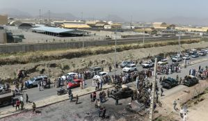 Afghan security forces and locals gather at the site of an attack by the Taliban on Kabul International Airport on July 17, 2014.(AFP Photo/Shah Marai)