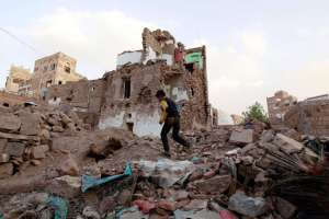 A Yemeni boy runs past buildings damaged by air strikes carried out by the Saudi-led coalition in the UNESCO-listed old city of the Yemeni capital Sanaa.