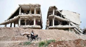 A man in Syriamn village in central Syria passing by a destructed building
