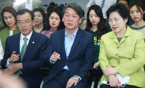 Ahn Cheol-Soo (C), co-chairman of the opposition People's Party of Korea, with party members, watch a television report on an exit poll of the new members of the National Assembly.