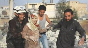 Cicilians and paramedics rescuing an injured woman following an air raid waged by Assad's regime north Aleppo