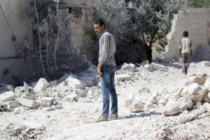 A man inspects the damage at a site hit by an airstrike in the rebel-controlled area of Jarjnaz village in Idlib province