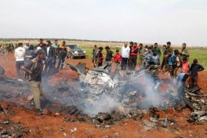 Fighters and civilians gather around the wreckage of a Syrian warplane that was shot down in the Talat al-Iss area, south of Aleppo