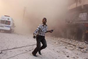 A man holding walkie-talkies runs towards a site damaged by what activists said were barrel bombs dropped by warplanes loyal to Syria's President Assad, in Aleppo