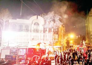 Smoke rises as Iranian protesters set fire to the Saudi embassy in Tehran on Jan 3