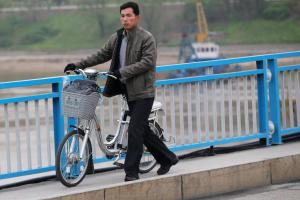 A man pushes an electric bicycle over the bridge in Pyongyang