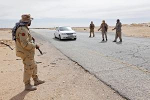 Libyan soldiers manning a military outpost, stop a car at a checkpoint in Wadi Bey, west of the city of Sirte, which is held by ISIS militants