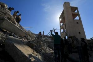 People and Civil Defense members remove rubble while looking for survivors in the ruins of a destroyed Medecins Sans Frontieres (MSF) supported hospital hit by missiles in Marat Numan, Idlib province, Syria