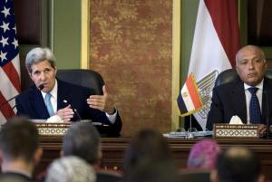 Egyptian Foreign Minister Sameh Shukri listens as U.S. Secretary of State John Kerry delivers a speech during a news conference after meetings at the Ministry of Foreign Affairs in Cairo