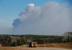 A fire truck drives down a highway in front of the Fort McMurray wildfires in Kinosis