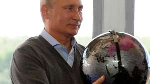 Russian President Vladimir Putin holds a terrestrial globe presented him as a gift in Tver region, Russia, on Friday. Mikhail Klimentyev.