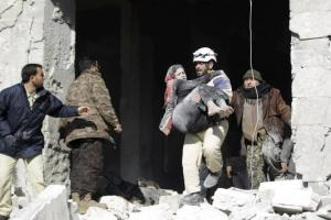 A civil defence member carries an injured woman in a site hit by what activists said were airstrikes carried out by the Russian air force in the rebel-controlled area of Maaret al-Numan town in Idlib province, Syria