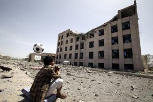Houthi militant sits amidst debris from the Yemeni Football Association buildin in Sanaa