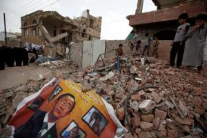 A defaced poster of the U.N. Secretary-General Ban Ki-moon is seen on the rubble of a house during a vigil marking one year since a Saudi-led air strike on a residential area in Sanaa, Yemen