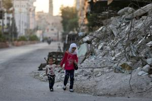 Children walk past the rubble of damaged buildings on Eid al-Fitr, which marks the end of the holy month of Ramadan, in the rebel held Douma neighbourhood of Damascus